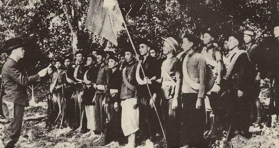 Buổi lễ thành lập đội Việt Nam Tuyên truyền Giải phóng Quân; Võ Nguyên Giáp (bìa trái), Hoàng Văn Thái cầm cờ