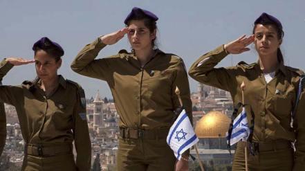Những nữ binh Israeli đứng chào trước mộ chiến sĩ trận vong, tại một nghĩa trang quân đội trên Đồi Olive, nhìn xuống thành cổ Jerusalem. Ảnh chụp hôm 14, 4. 2013 của AP/Sebastian Scheiner