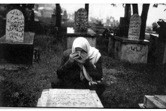 """Một người Palestine khóc trước mồ người thân. Bia mộ bên phải ghi """"Ramla"""", một thành phố bị các đơn vị bán vũ trang Israel càn quét vào cuối những năm 1940s và sau đó chuyển sang bị chính quyền Israel cai trị vào đầu năm 1949. Đây nhiều phần là nghĩa trang của những người Palestine tị nạn. Ảnh và chú thích từ trang Smpalestine"""