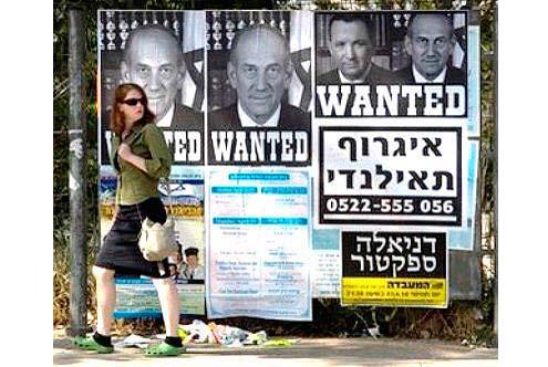 Poster truy nã Ehud Olmert (có hai poster riêng) và Ehud Barak (cả hai đều từng là cựu Thủ tướng Israel) tại Jerusalem, tháng Tư 2010. Olmert và Barak bị cáo buộc ăn hối lộ và tham nhũng. Theo Văn phòng Tổng chưởng lý Israel, trong thời gian trước khi được bầu làm Thủ tướng Israel năm 2006, ông Olmert nhận hàng trăm nghìn USD bất hợp pháp của doanh nhân người Mỹ gốc Do Thái Morris Talansky