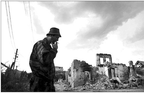 Một người dân Nam Ossetia trước một khu phố ở thủ phủ Tskhinvali bị tàn phá khi quân đội Grudia tấn công vào đây.