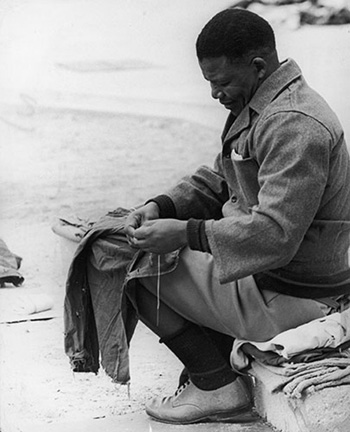 Mandela khâu áo trong sân nhà tù năm 1966.