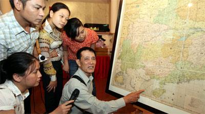 Tiến sĩ Mai Hồng giải thích cho người xem nội dung chữ Hán cổ trên bản đồ của Trung Quốc năm 1904 mà ông đã hiến tặng Bảo tàng Lịch sử quốc gia. Ảnh: TTO