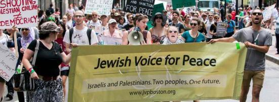 """Phản đối chiến tranh tại Hoa Kỳ bởi người Do Thái Mỹ, Hai người mang băng rôn đeo cờ Palestine (trên cổ tay và trên ngực) Biểu ngữ đề """"Tiếng nói Do Thái cho Hoà Bình: Người Israel và người Palestine. Hai dân tộc. Một tương lai"""""""