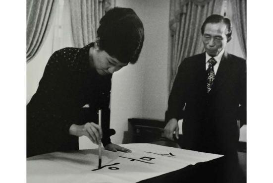 Bà Park Geun Hye dùng bút lông viết thư pháp tiếng Triều Tiên, bên phải là cha của bà: Tổng thống Park Chung Hee. Ảnh chụp tại Seoul vào 31 tháng Tám năm 1977, lúc này bà Park đang phải nhận cương vị Đệ nhất Phu nhân vì mẹ bà đã bị bắn chết trong một vụ ám sát hụt ông Park năm 1974. Ông Park thuộc thế hệ được đào tạo tại Nhật, còn bà Park thuộc thế hệ học xong Cử nhân hoàn toàn tại Hàn Quốc.