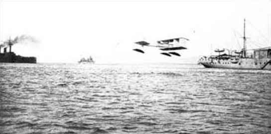 Chiếc tàu sân bay thủy phi cơ đầu tiên của Pháp La Foudre ( ở bên phải, với nhà chứa máy bay và cần cẩu), với một trong những thủy phi cơ Canard Voisin của nó đang cất cánh, trong các bài tập chiến thuật vào tháng 6 năm 1912