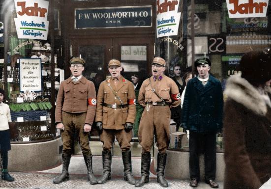 Đoàn viên Đoàn Thanh Niên Áo Nâu đứng trước một cửa tiệm bán đồ chơi của người Do Thái để làm cho khách hàng sợ không dám vào